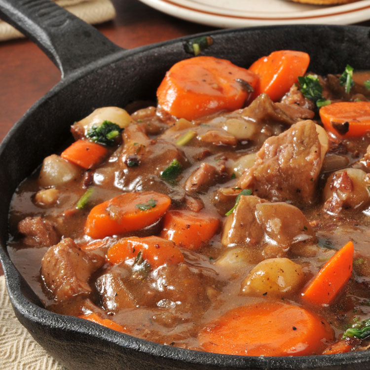A skillet of beef stew with carrots pearl onions and mushrooms in a burgundy wine sauce